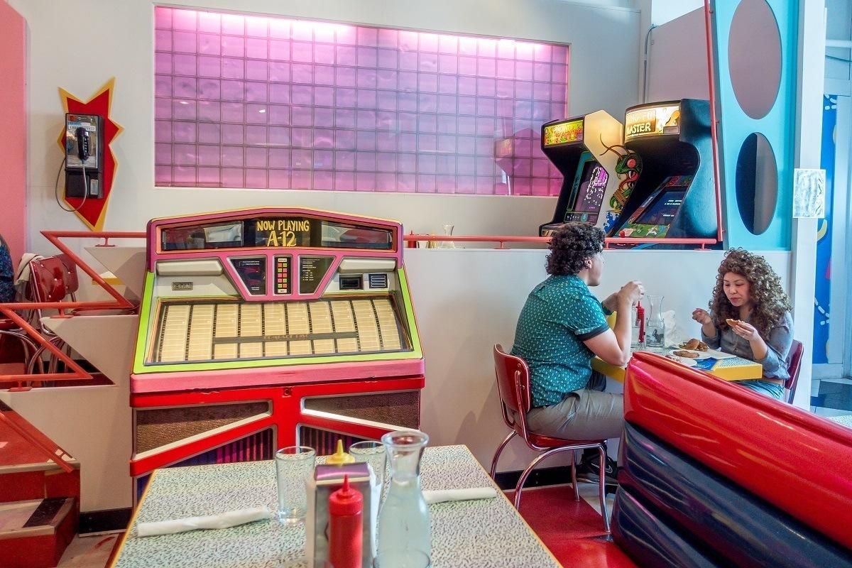 People eating in diner by a jukebox