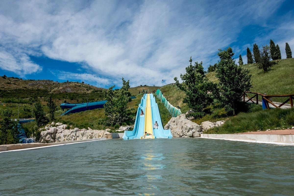 People on a hillside water slide