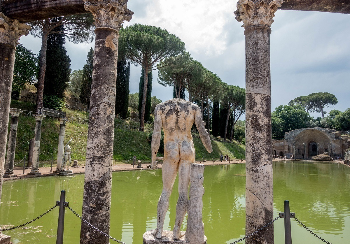 Headless statue and columns by a large pool