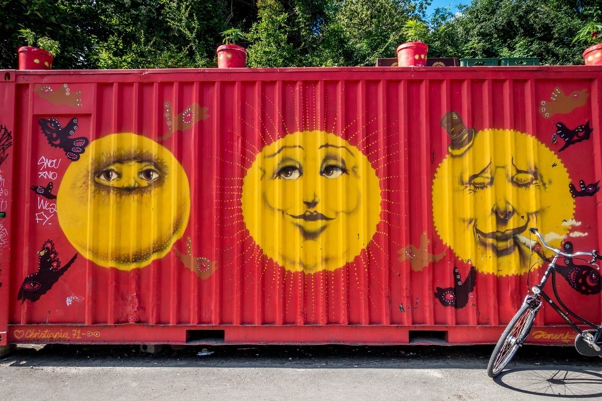 Container painted red with three large yellow faces