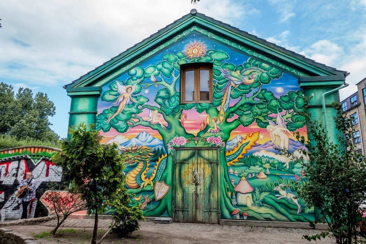 Mural of tree and fairies at the entrance to Freetown Christiania in Copenhagen Denmark