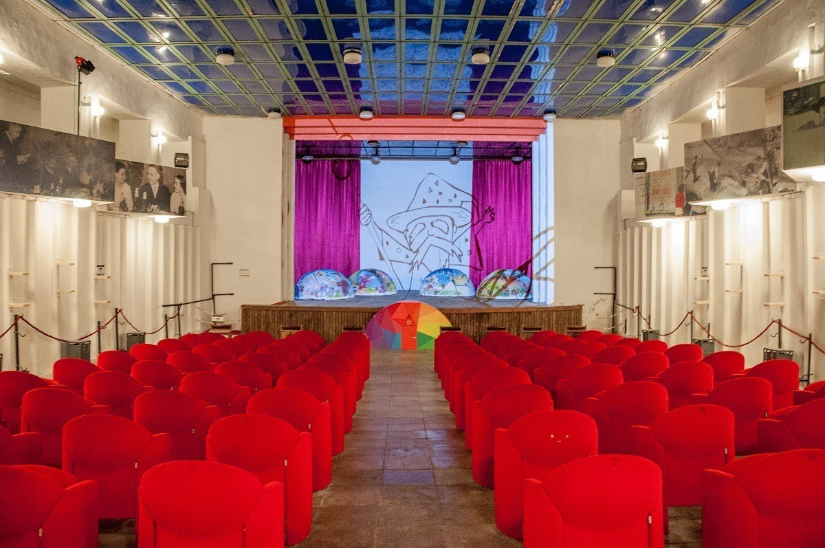 Room with red chairs and movie screen in museum