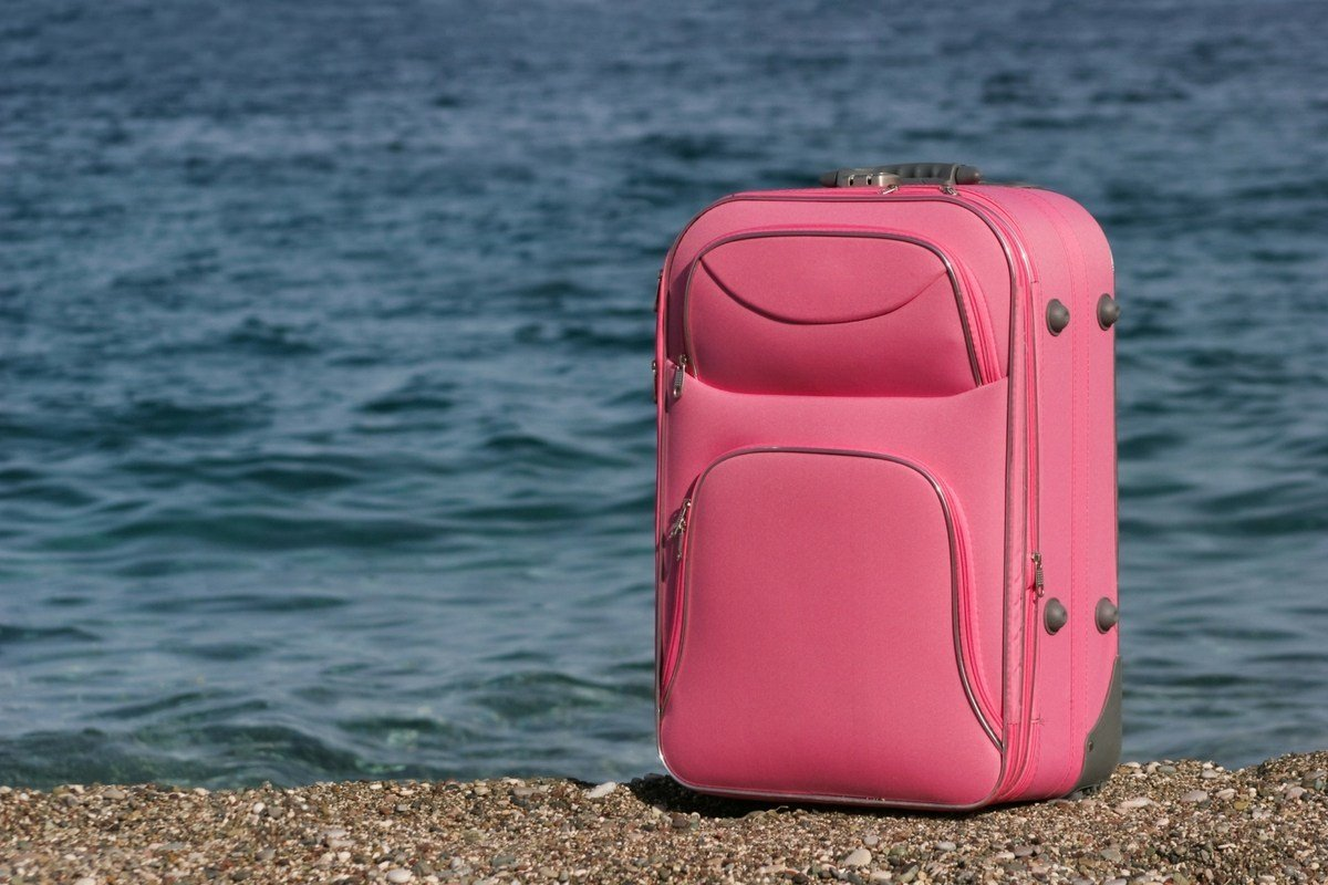 Pink luggage by water