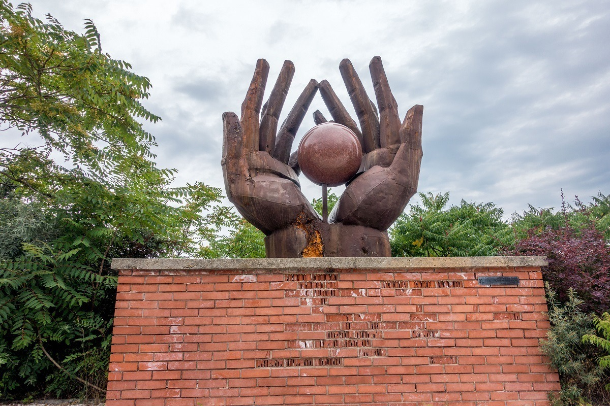 Sculpture of two hands holding a sphere