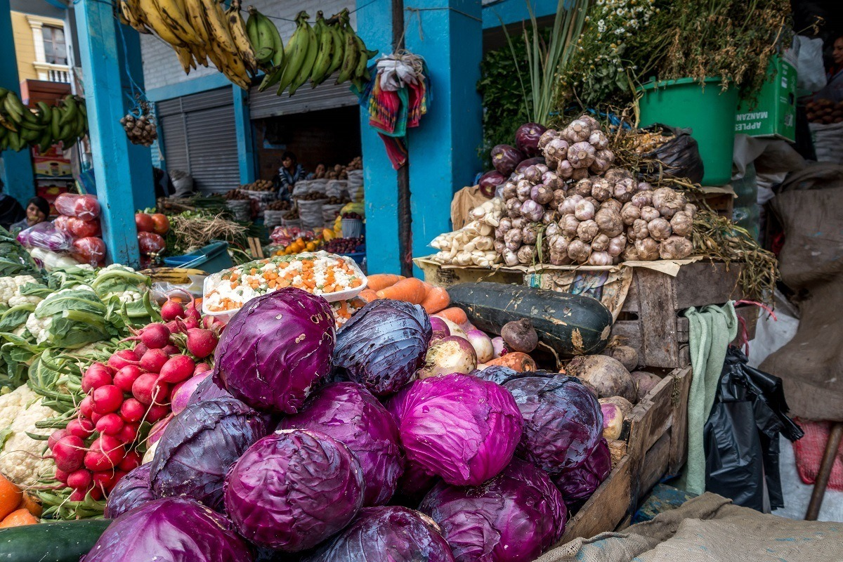 Piles of cabbage and radishes at an outdoor market
