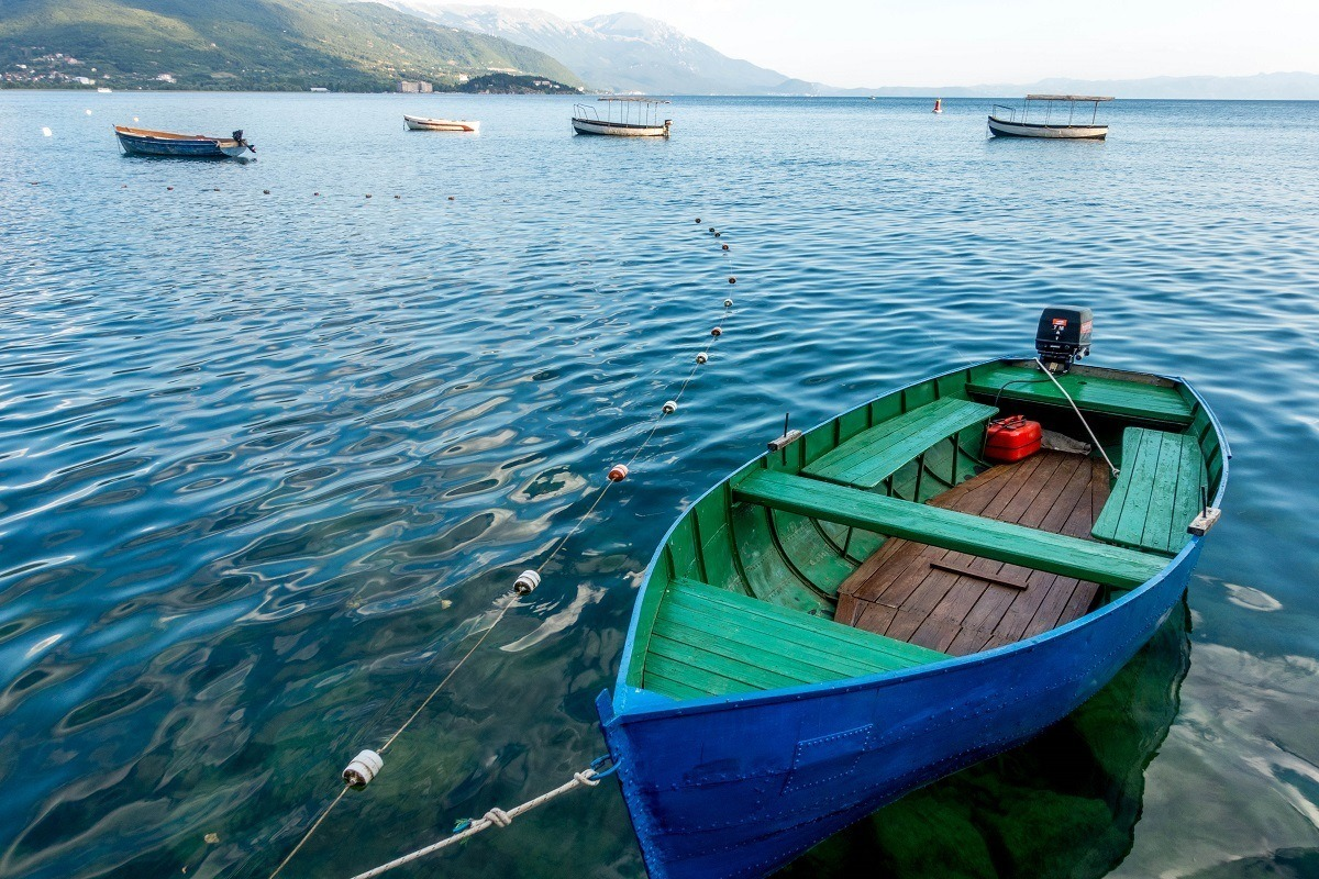 A small blue and green boat on the water