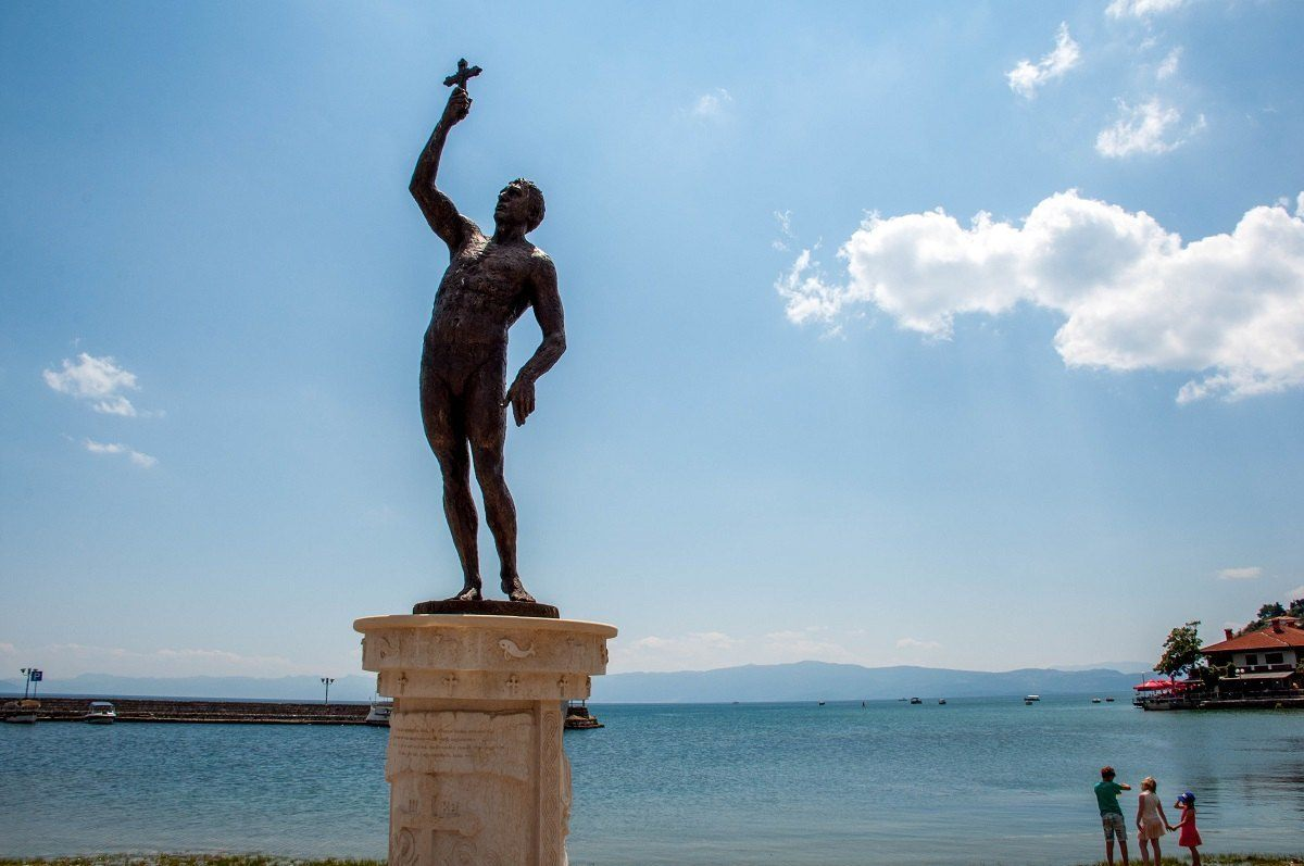 Statue on the shore of Lake Ohrid of man holding a cross