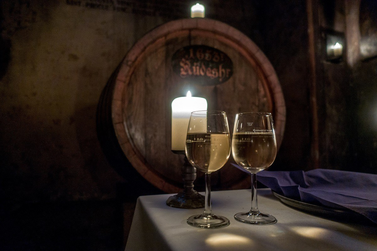 Two wine glasses lit by a candle by a wine barrel