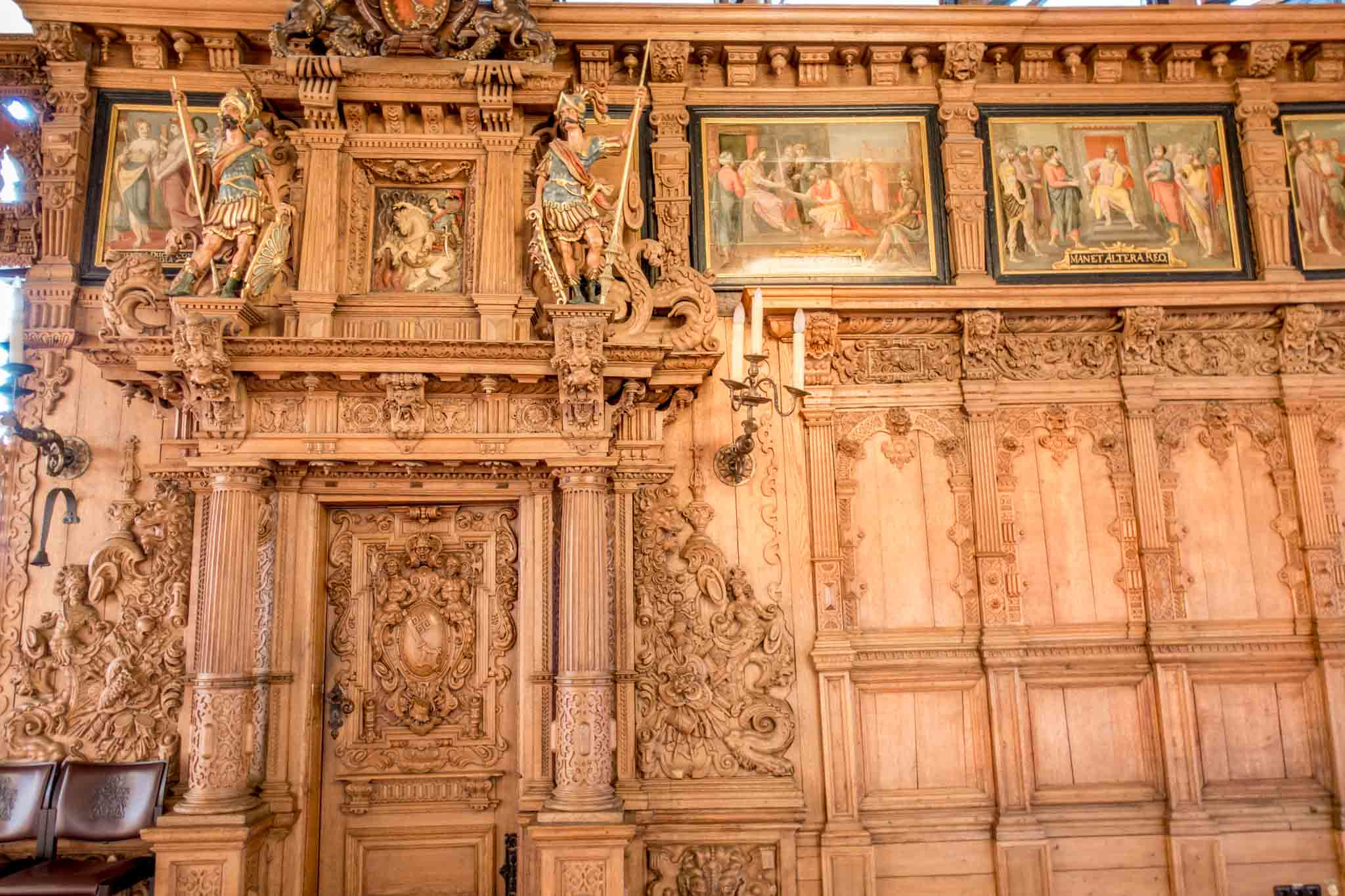An intricately-carved wood wall with paintings