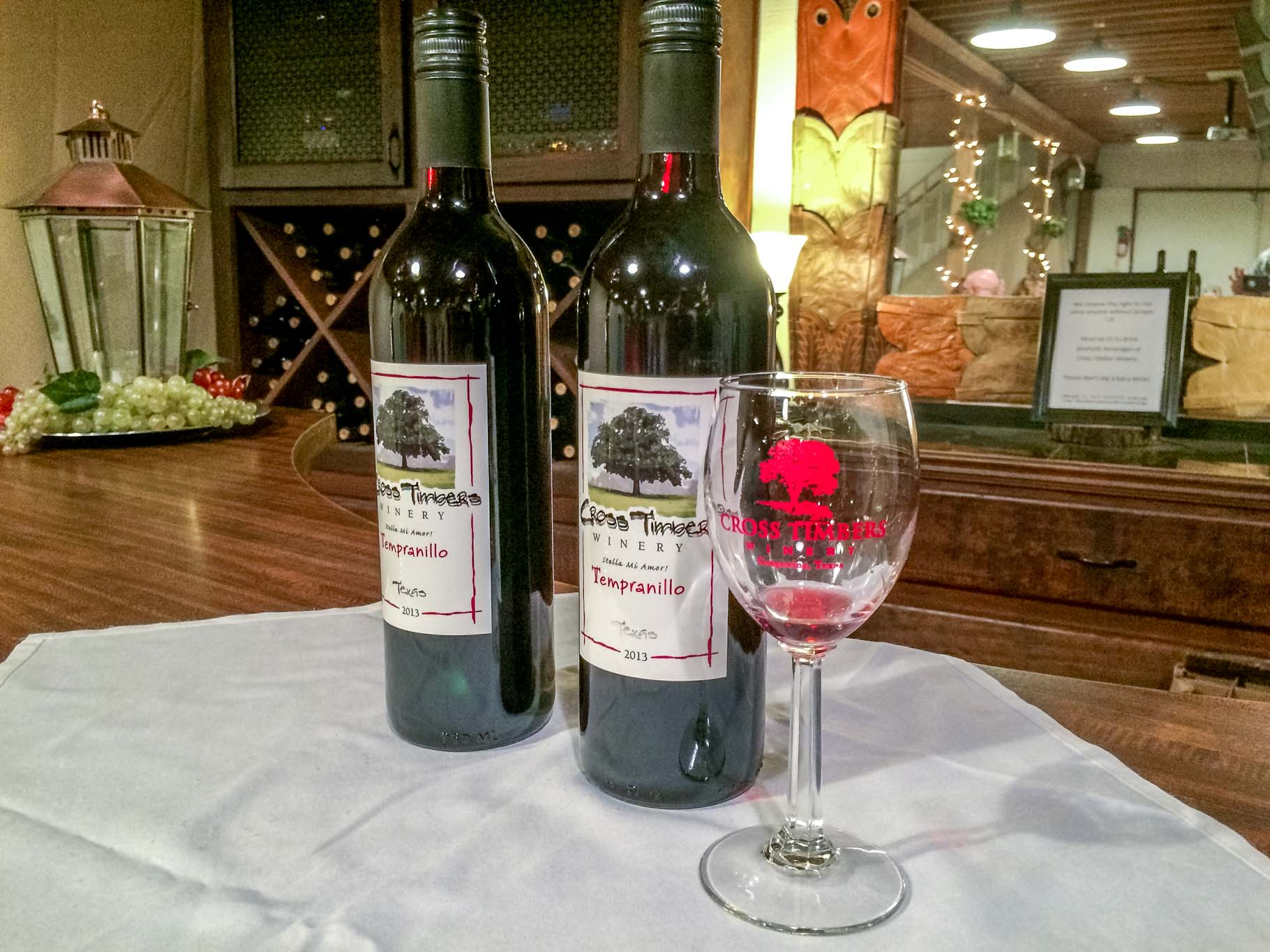 Wine bottles and glass at Cross Timbers Winery