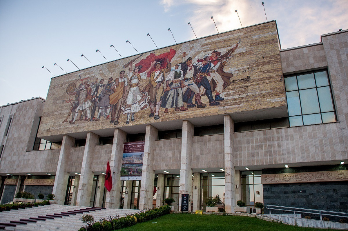 Exterior of a building with a mosaic showing a group of people