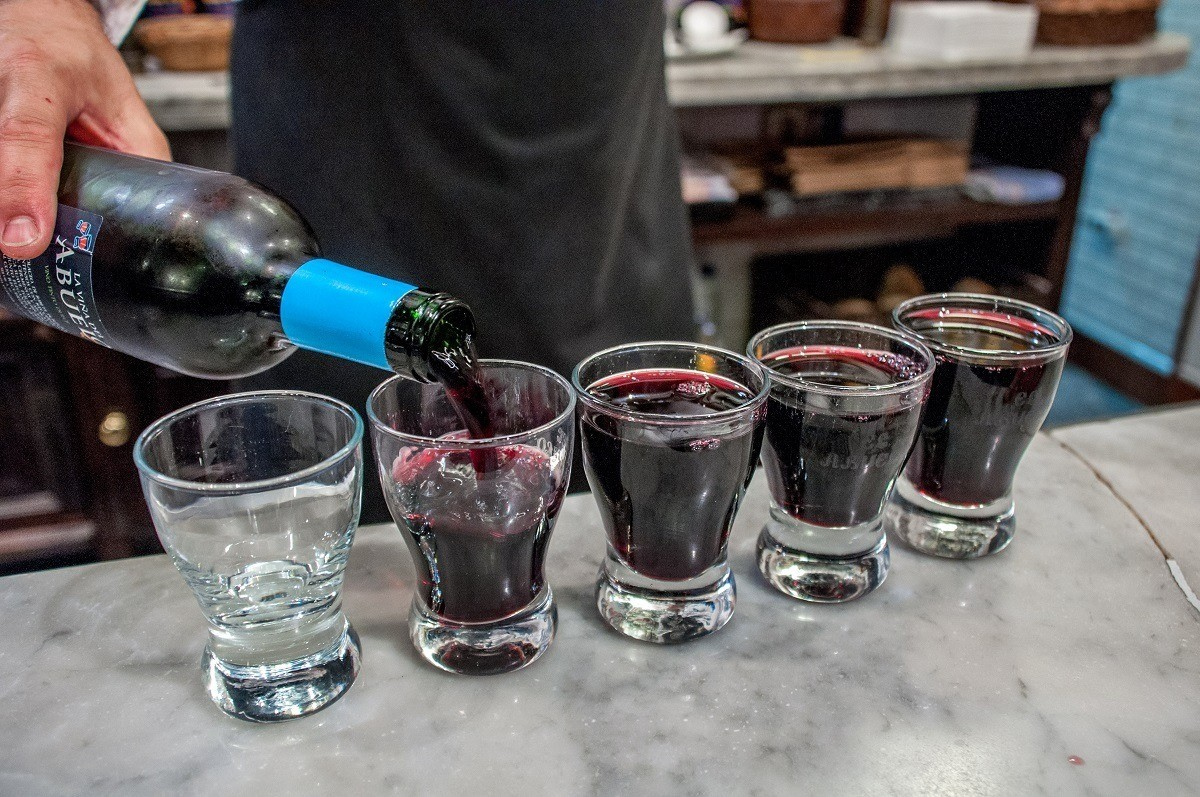 Person pouring red wine into glasses