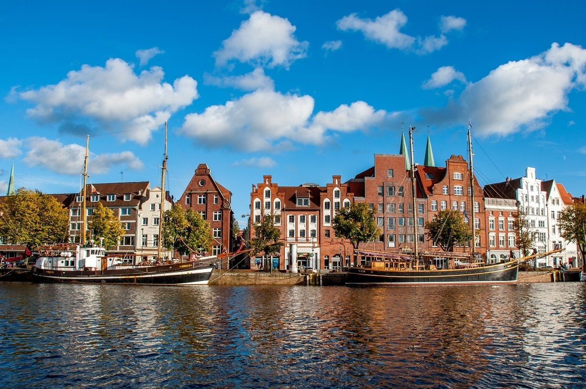 Boats in the Trave River and historic buildings in Lubeck Germany