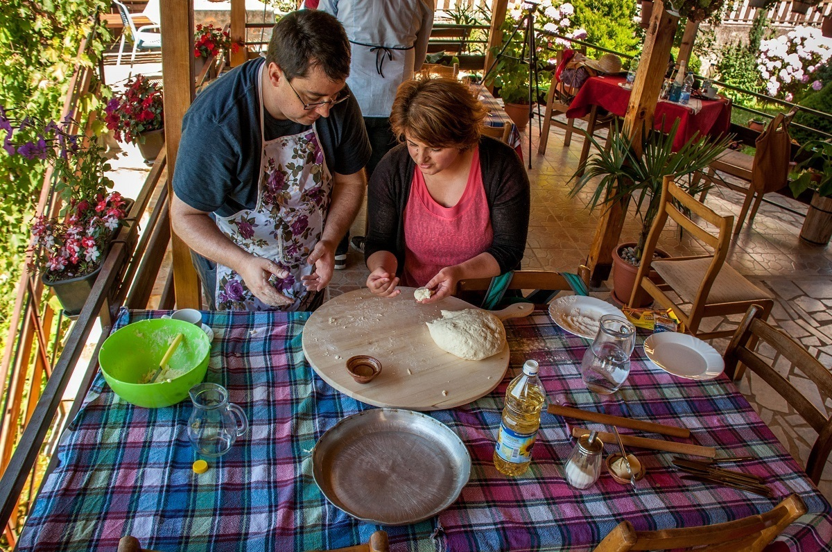 Anita of Risto's Guest House teaching Lance how to roll dough