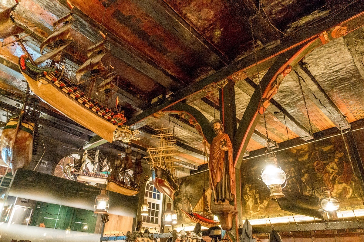 Ceiling with nautical themed items hanging from wooden beams