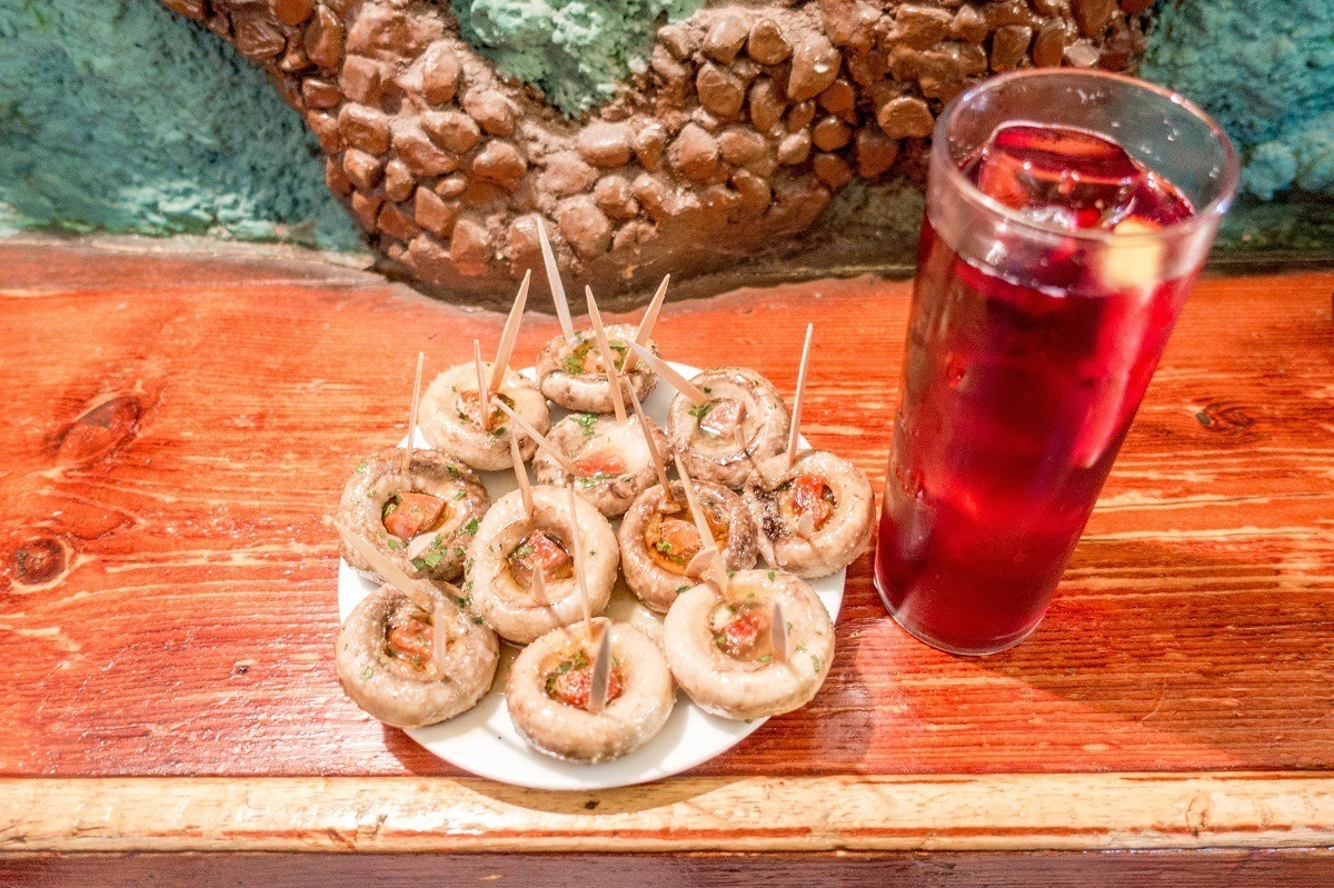 Mushrooms stuffed with chorizo and tinto de verrano on a food tour in Madrid, Spain