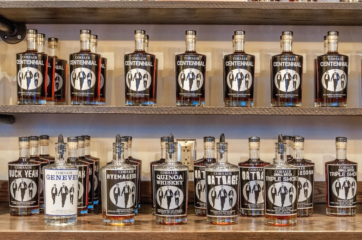 Shelf lined with bottles of whiskey at Corsair Distillery