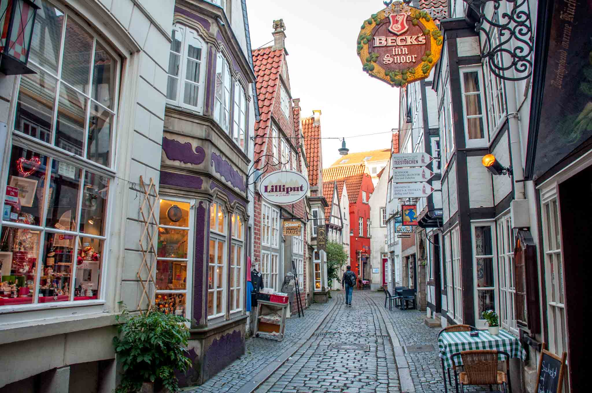 Narrow, cobblestone street and storefronts