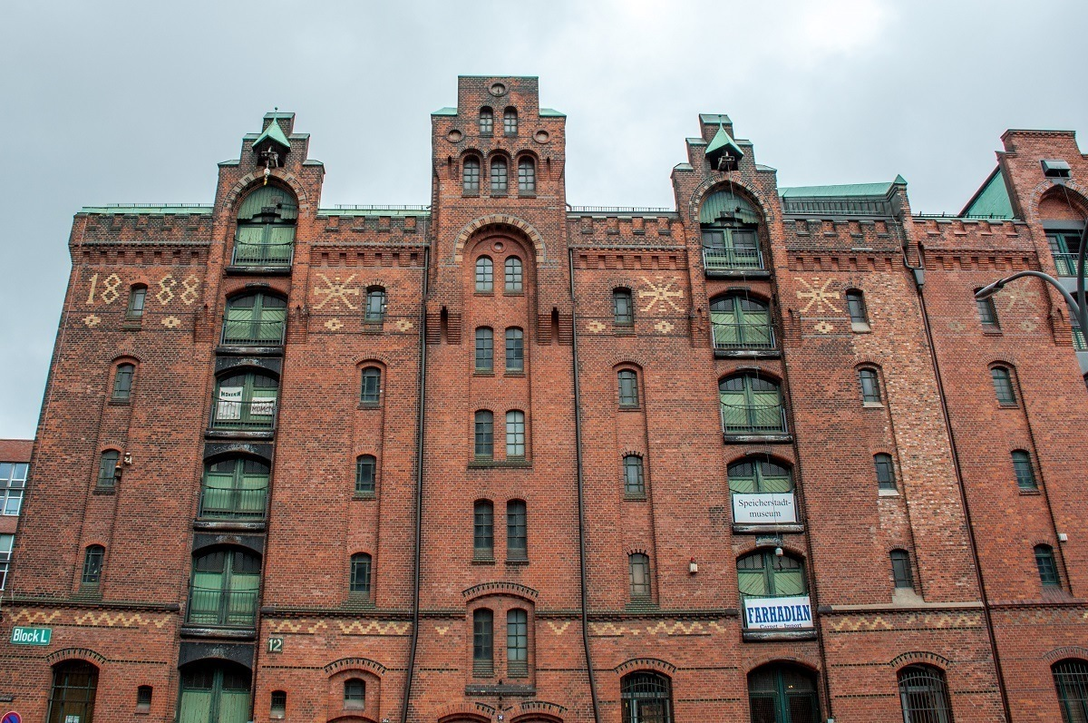 Red brick building with light colored graphic designs