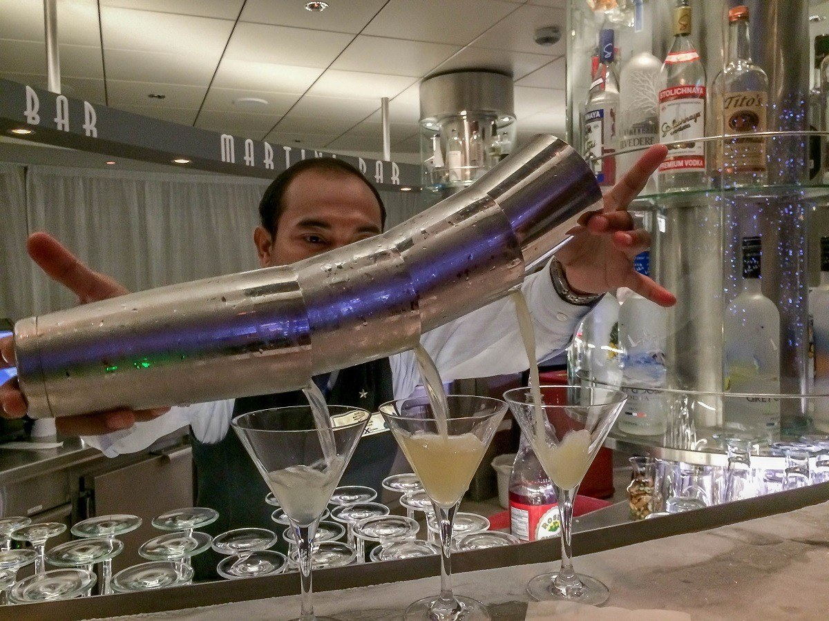 Bartender pouring cocktails into martini glasses