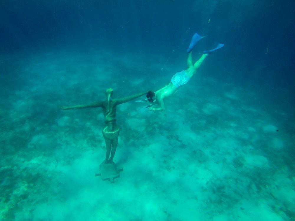 Person snorkeling near an underwater statue
