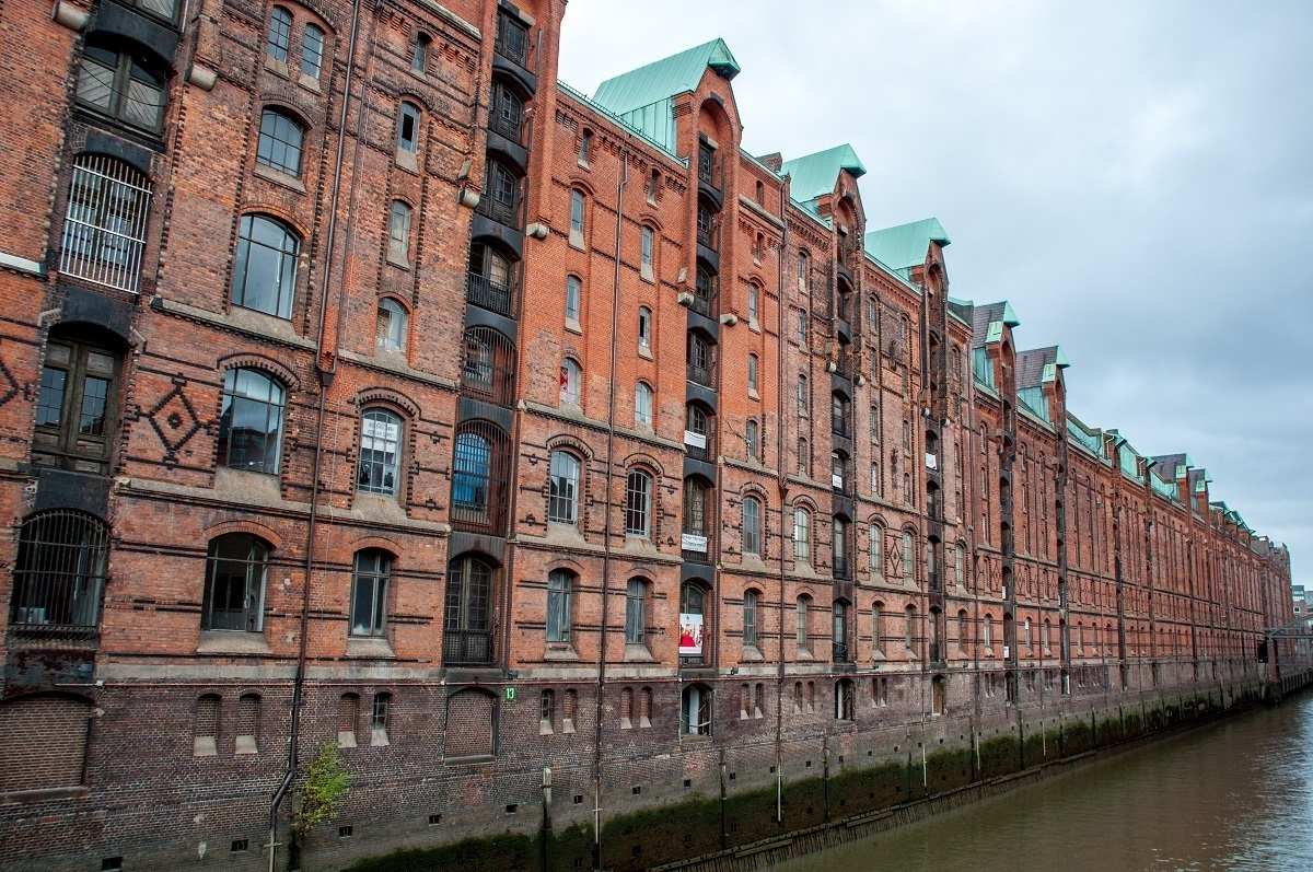 Long line of red-brick warehouses over a canal, part of the Speicherstadt district