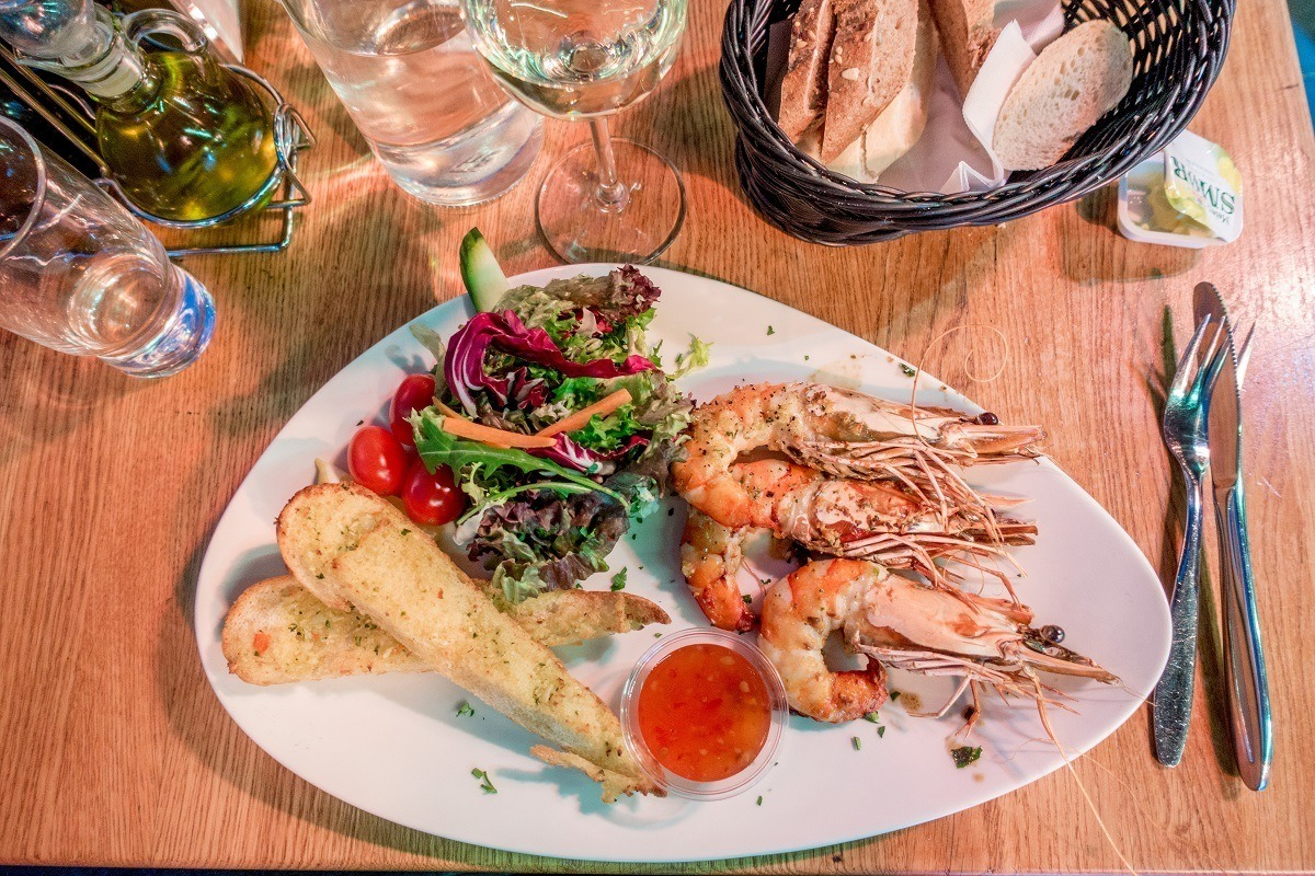 Shrimp, bread, and salad on a plate