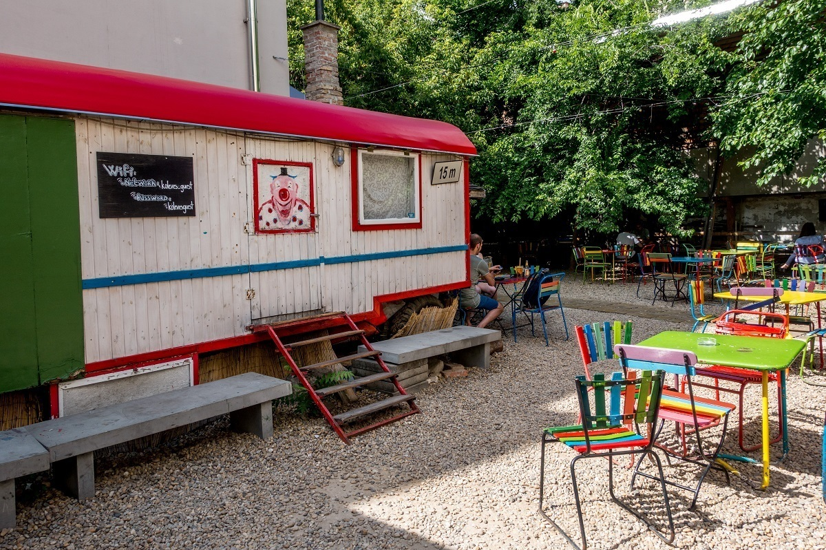 Colorful tables at an outdoor bar with a trailer