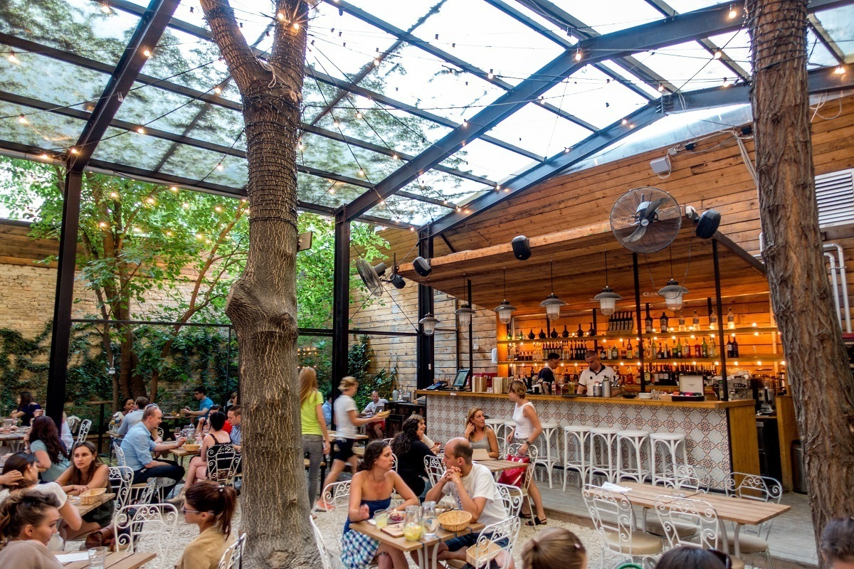 People eating at tables under trees beside a well-stocked bar