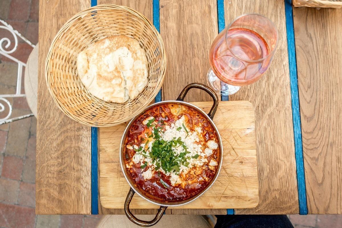 Shakshuka, bread, and wine on table