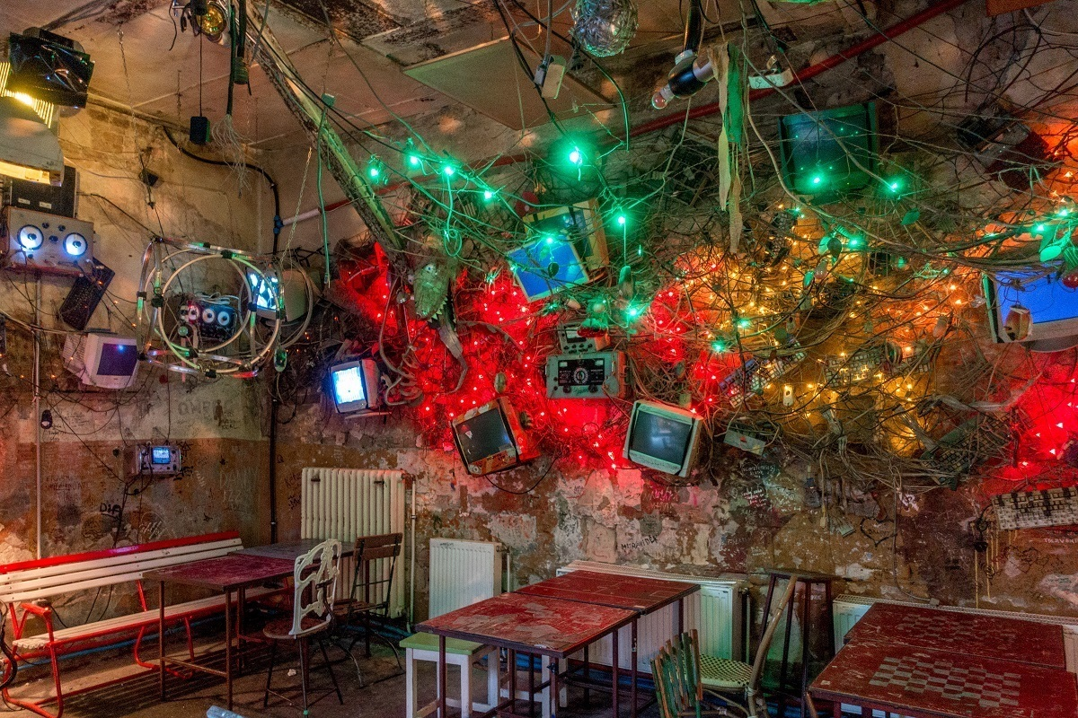 Christmas lights, computer monitors, and eclectic decorations in a dingy room