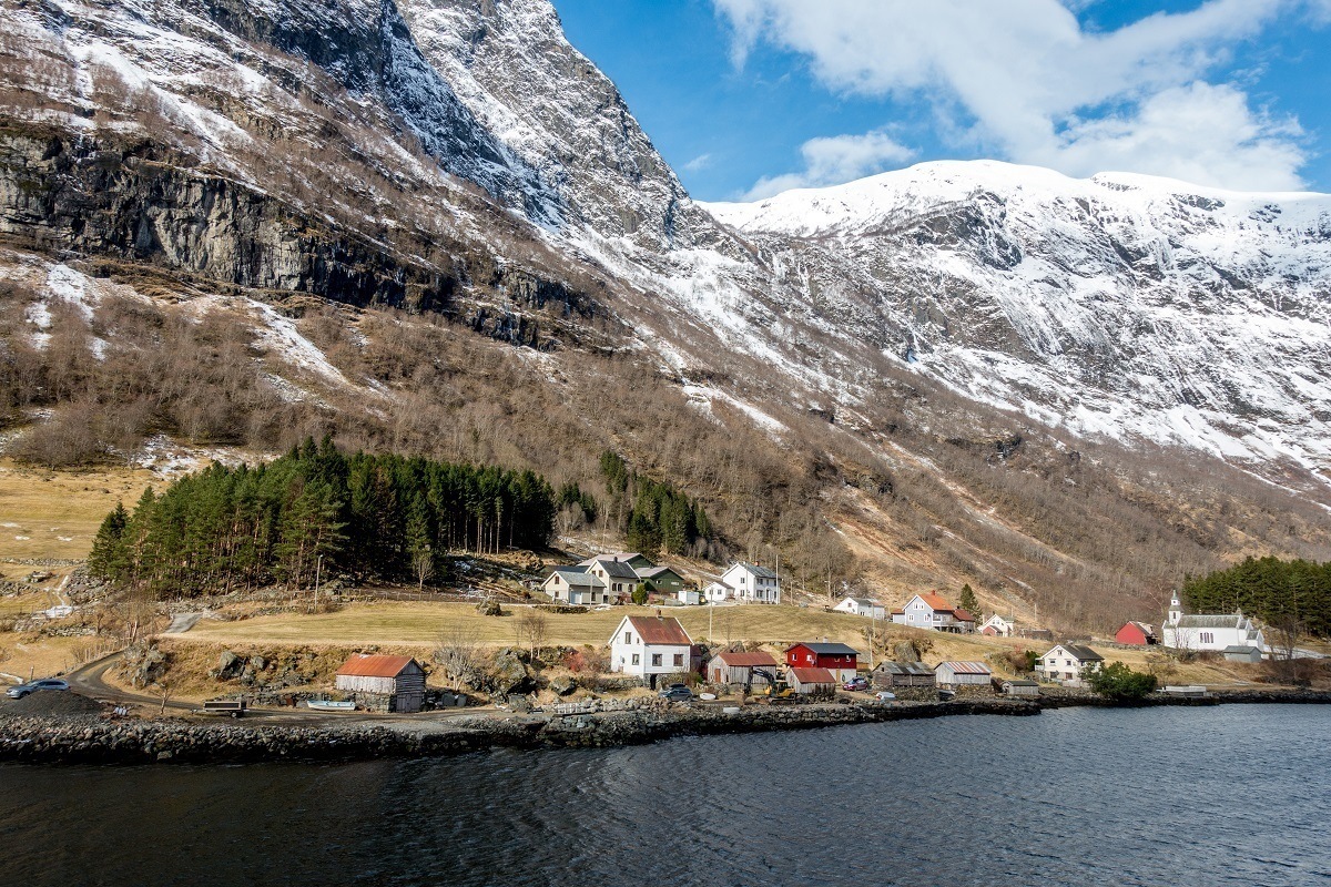 Houses along the water beside snow-covered mountains