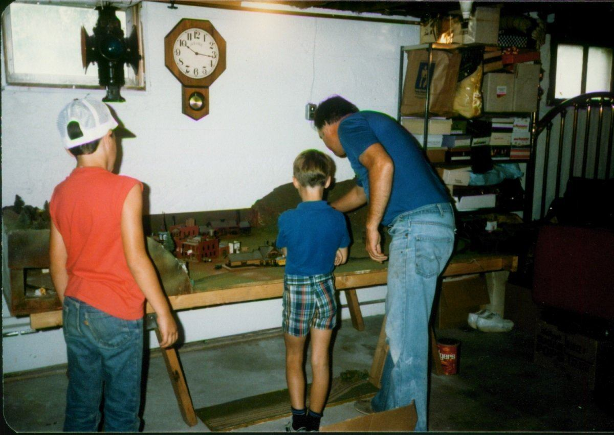 Lance working on train set with his dad and friend in 1984