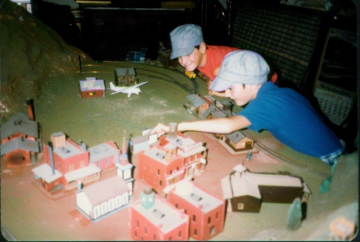 Lance and his friend Peter working on a model train set in 1984