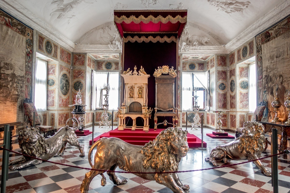 Royal thrones guarded by large silver lion statues