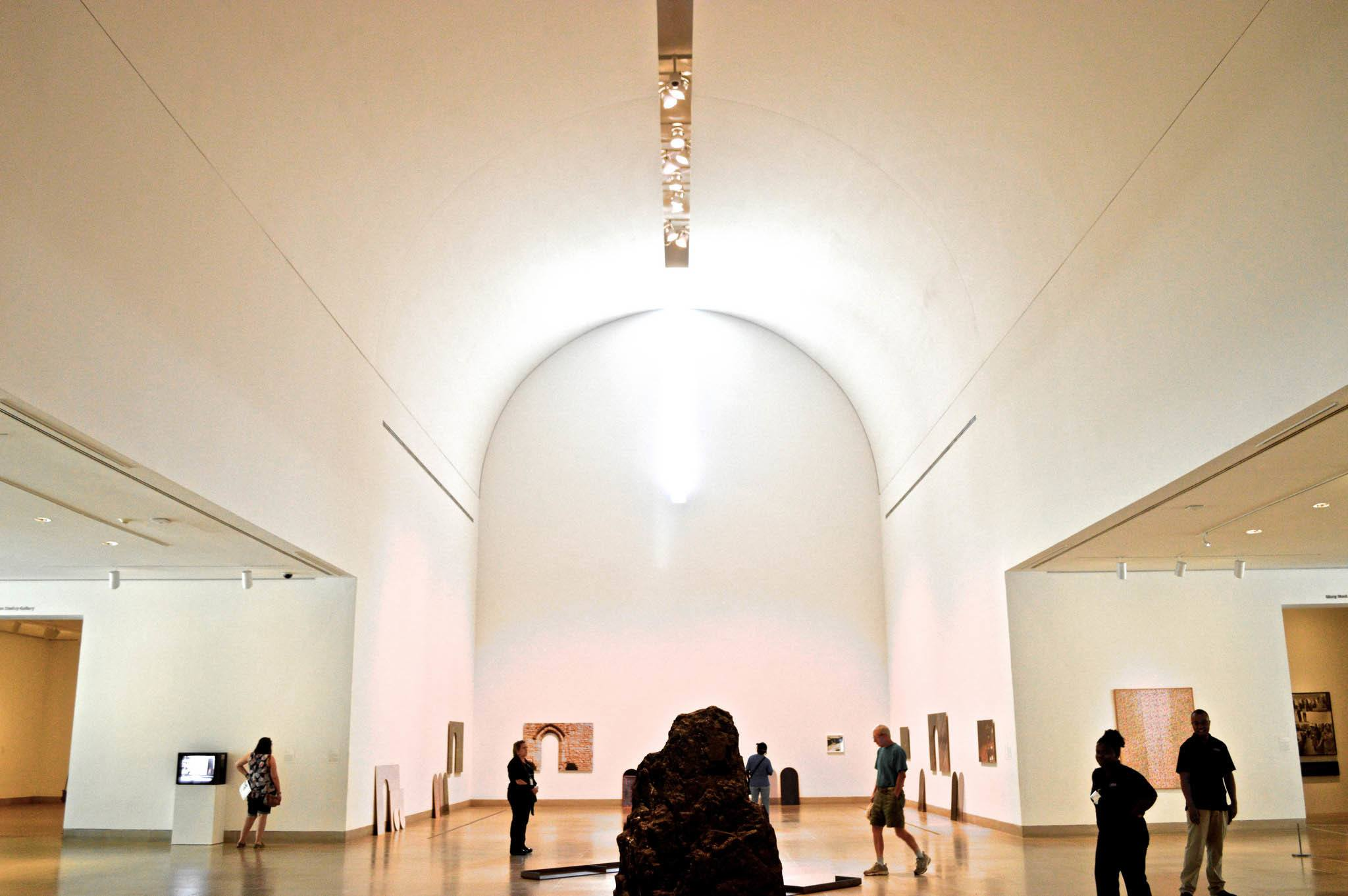 Large white rooms with paintings and visitors