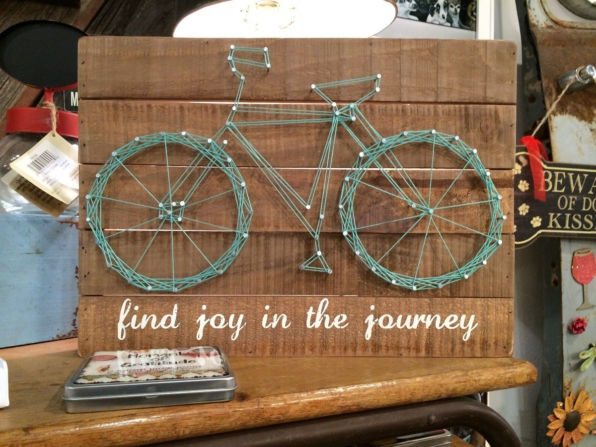 """Decoration featuring bicycle and labeled """"find the joy in the journey"""""""