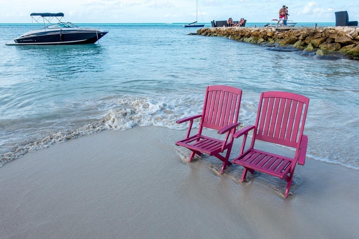 Beach chairs on the beach in Antigua near a rock jetty