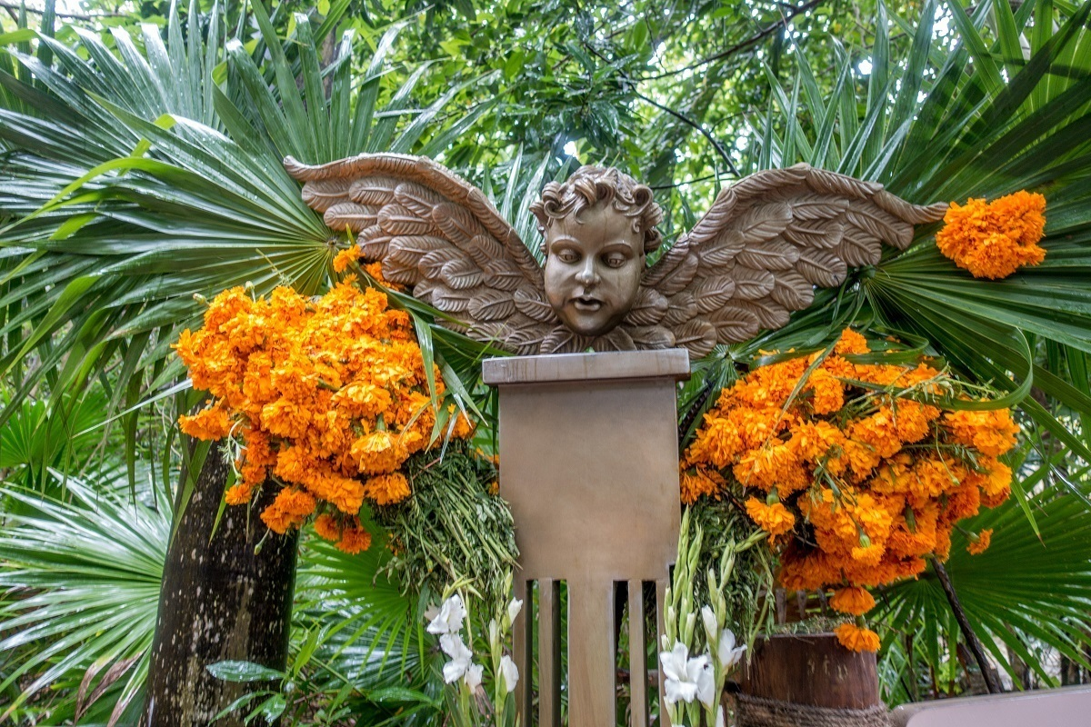 Memorial display with marigolds and a cherub