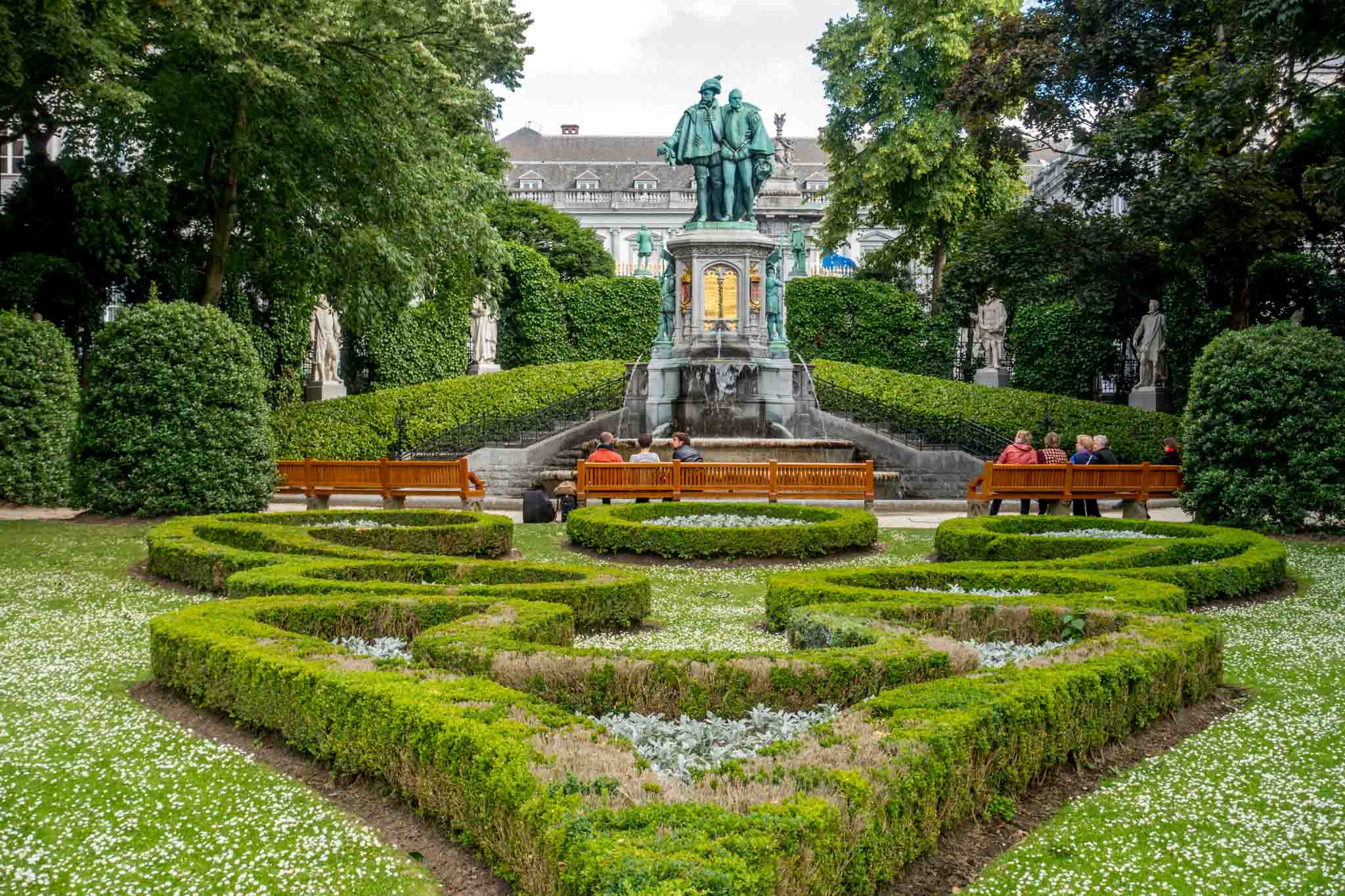 Park with manicured garden, fountain, and visitors on benches