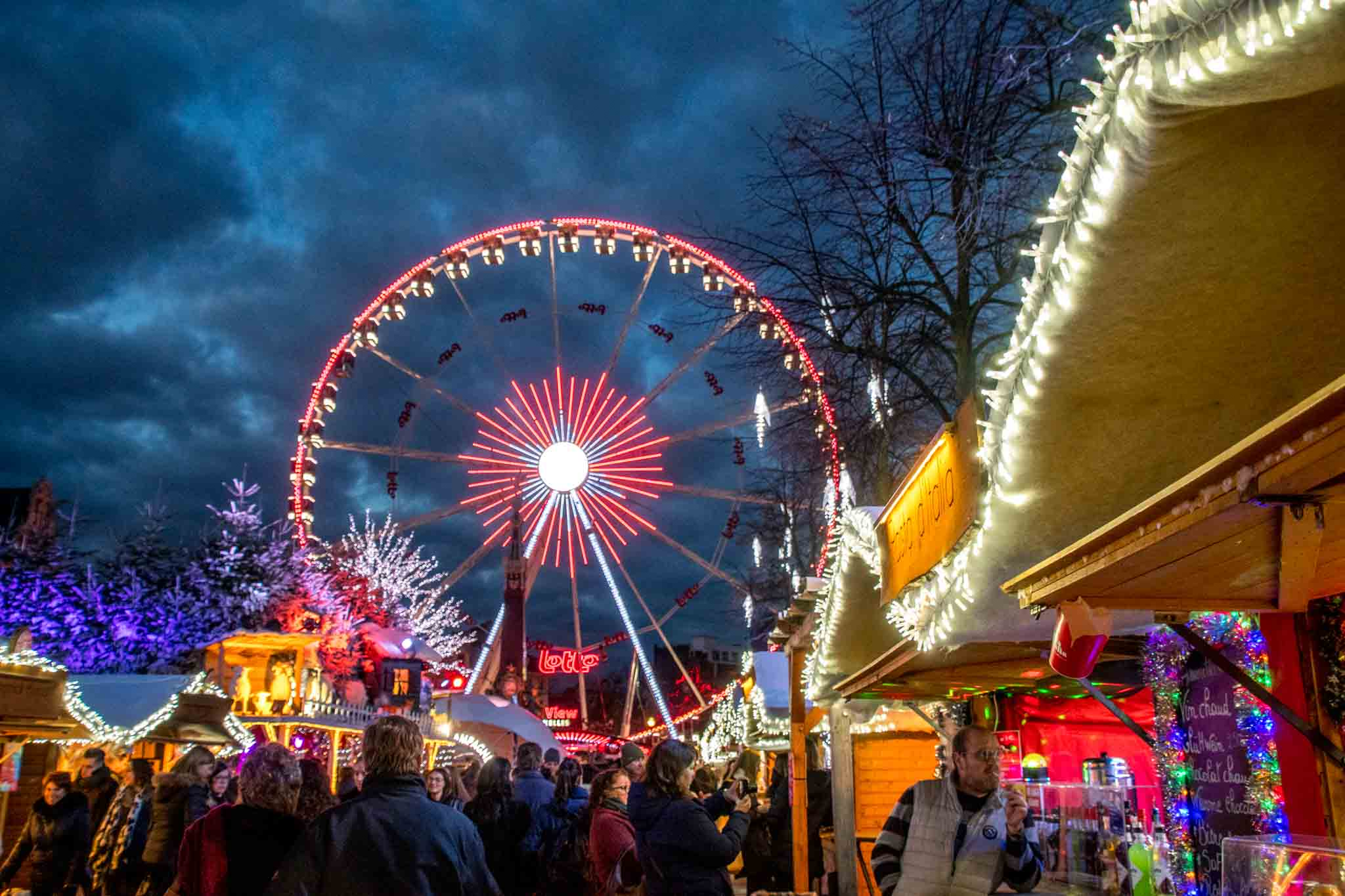 Ferris wheel, vendors, and shoppers at Christmas market