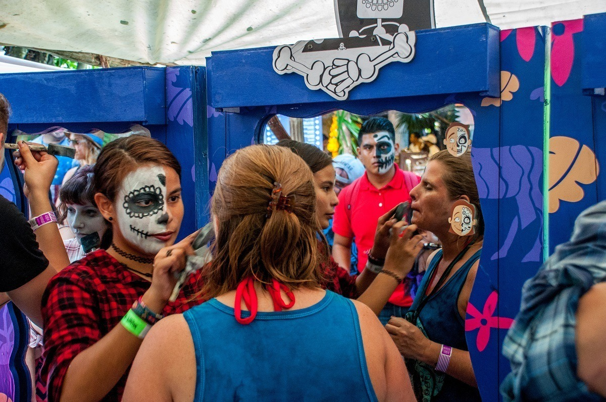People putting on Day of the Dead face paint