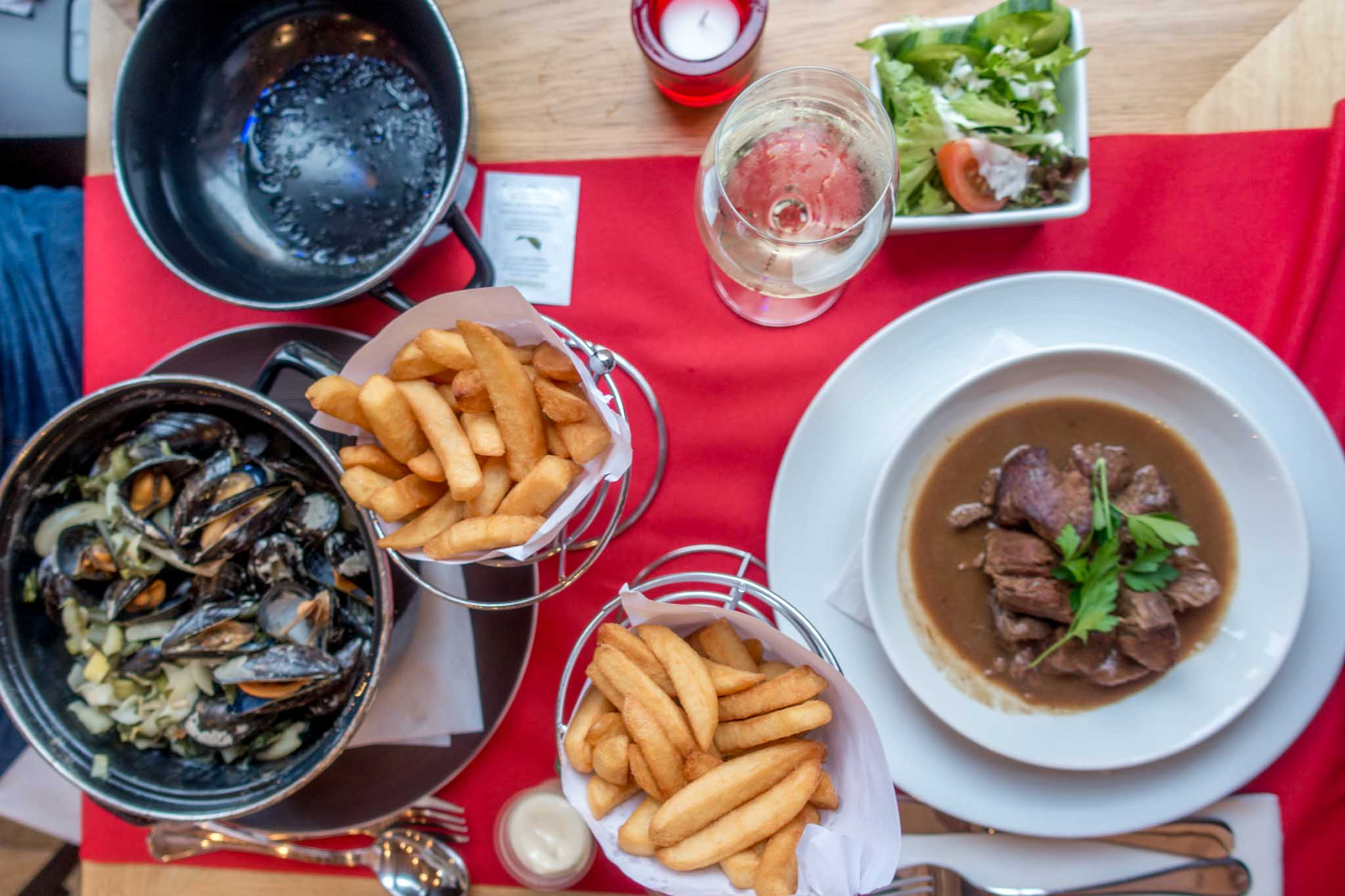 Frites, mussels, and other Belgian food on table