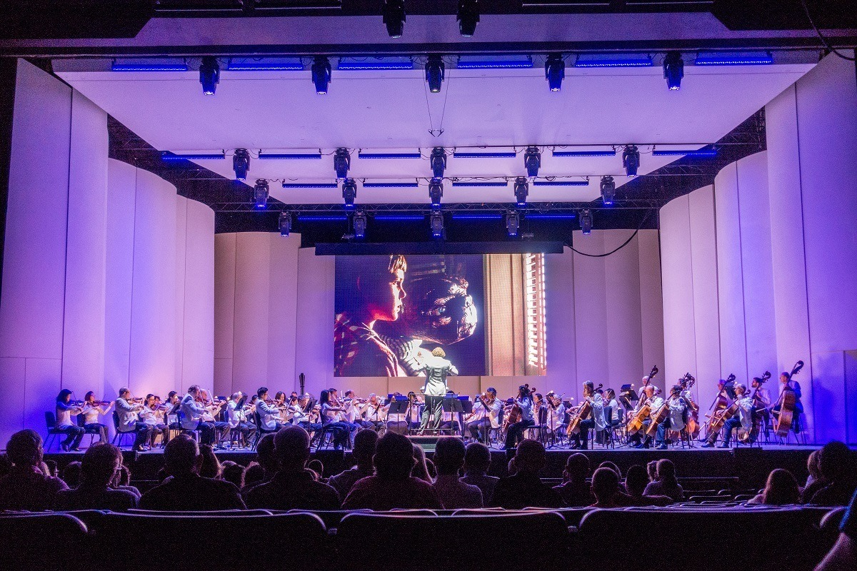 Orchestra playing while movie projects on a screen