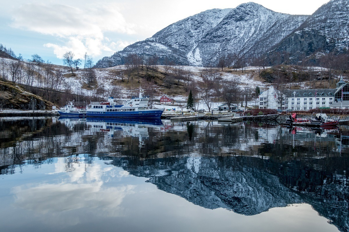 A boat in the harbor in Flam with a reflection of a mountain in the water