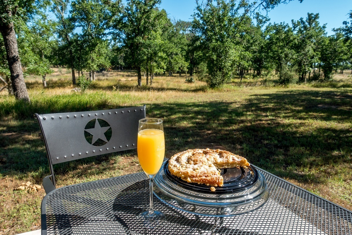 Pie and glass of orange juice on a table outside