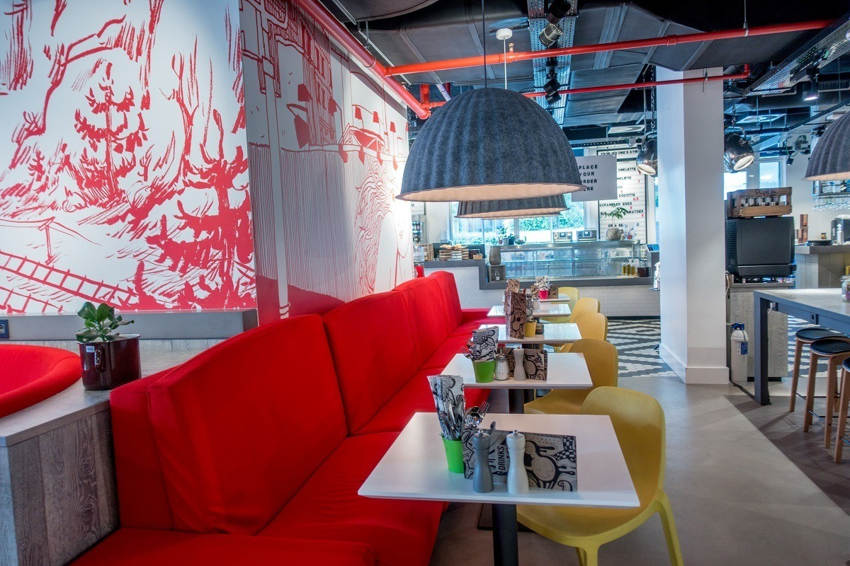 Hotel restaurant with red bench and cartoons on the wall