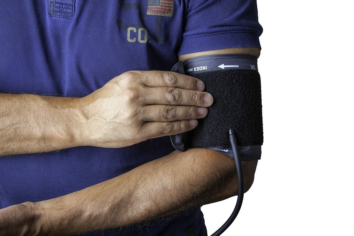 Man putting on blood pressure cuff