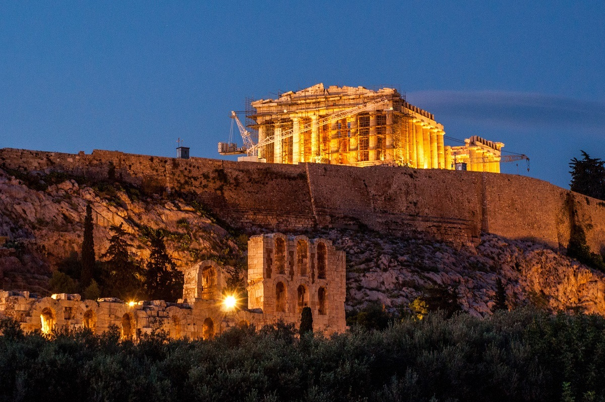 Ancient temple surrounded by scaffolding lit up at night