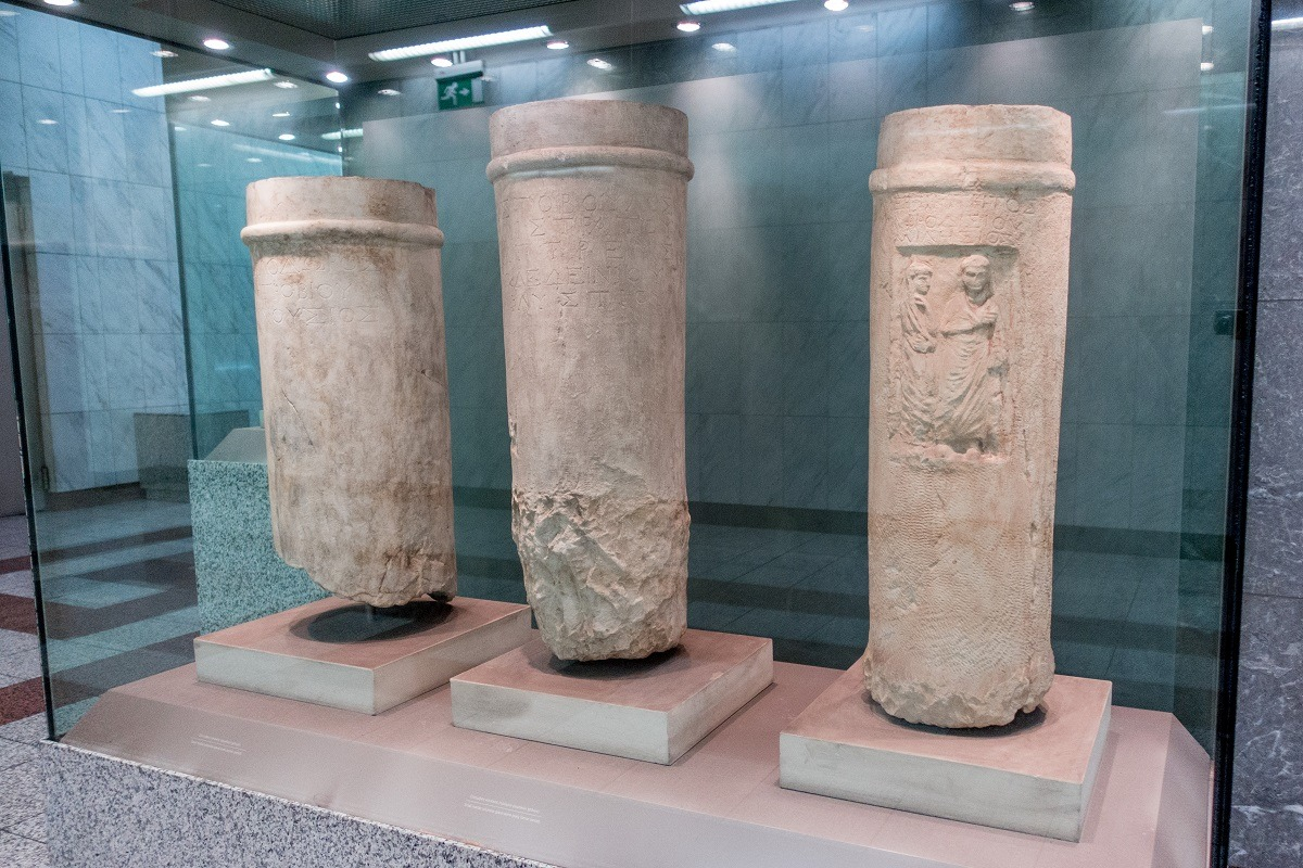 Ancient pillars displayed behind glass in the metro